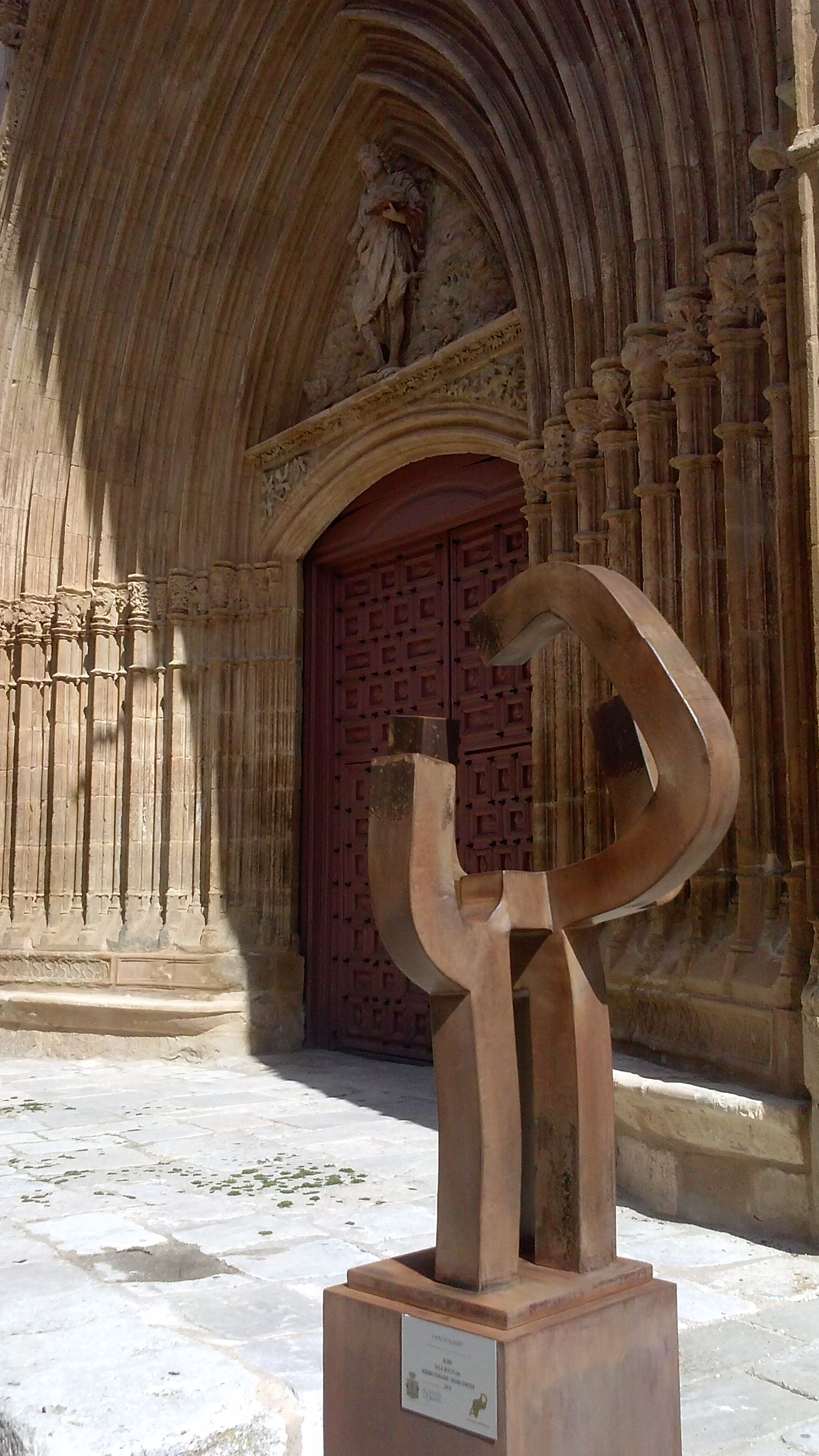 Almo, 163 X 38 X 35 cm, hierro forjado / Acero corten, 2015, pieza única. Como una sencilla aureola, la escultura se desarrolla a partir de un arco en la parte superior de la obra, homenaje a San Juan Bautista. Los tres apoyos verticales y el pedestal sobre el que se sitúa, aportan espiritualidad a la pieza.