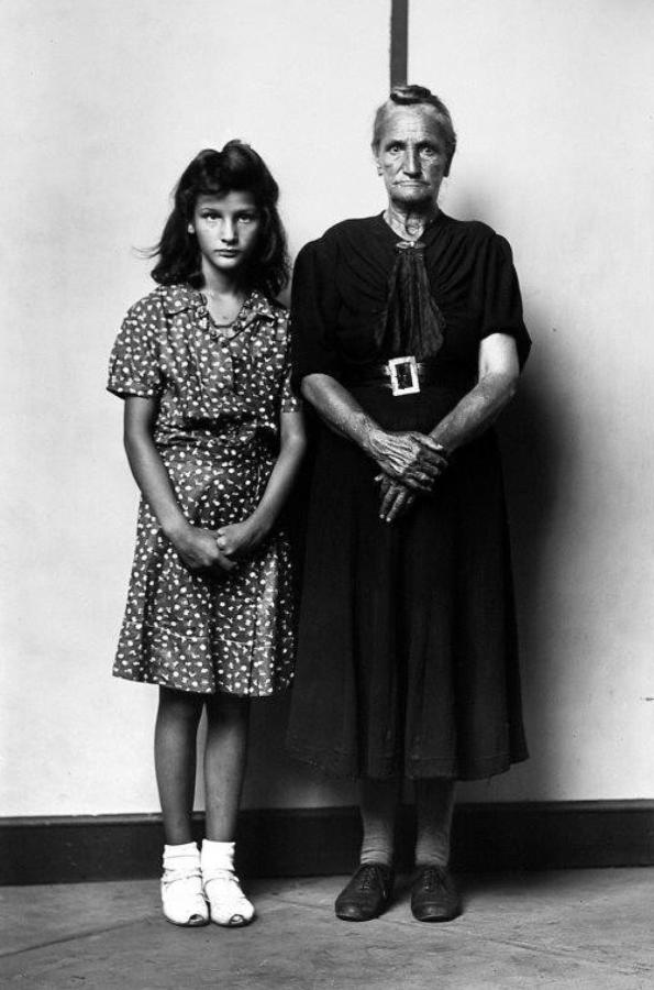 Sin título, por Mike Disfarmer (chica joven y abuela de pie con las manos apretadas delante de ellas), 1939-46, 36 cm x 30 cm.
