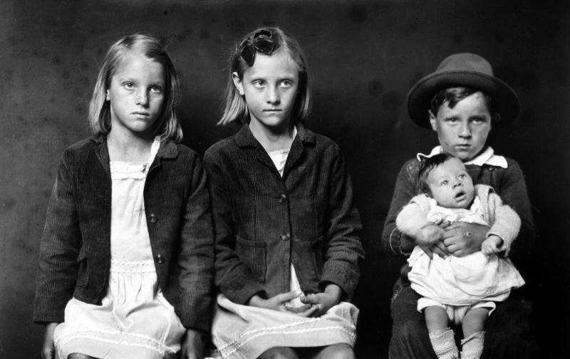 Sin título (dos niñas senatdas, niño de pie sosteniendo a un bebé), por Mike Disfarmer, 1939-46, 30 cm x 36 cm.