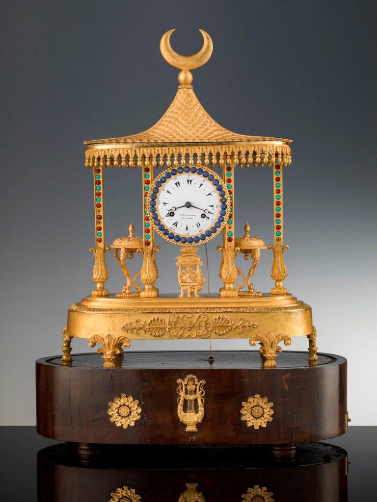 Reloj de sobremesa de Louis Courvoisier y Compañía, 1811-14, bronce dorado y esmalte policromado, en base de chapa de madera y bronce dorado, 57 × 42 × 23 cm, Florencia, Galería de los Uffizi, Galería de Arte Moderno del Palazzo Pitti.