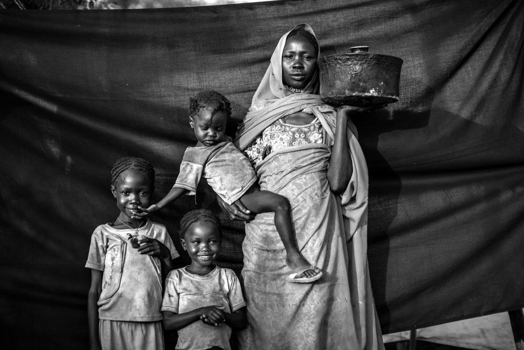 Magboola, 20 años, en el campamento de refugiados de Jamam, Maban, Sudán del Sur. Ella y su familia resistieron varios ataques aéreos durante meses, pero decidieron huir de su pueblo, Bofe, la noche en que los soldados se presentaron en él abriendo fuego. Junto con sus tres hijas, viajó durante doce días desde Bofe, en el estado sudanés de Nilo Azul, hasta la localidad de El Fudj, en la frontera de Sudán del Sur. Lo más importante que se llevó consigo es la olla que sostiene en esta fotografía, lo suficientemente pequeña como para poder viajar con ella y lo suficientemente grande como para cocinar el sorgo para ella y sus tres hijas durante el viaje.