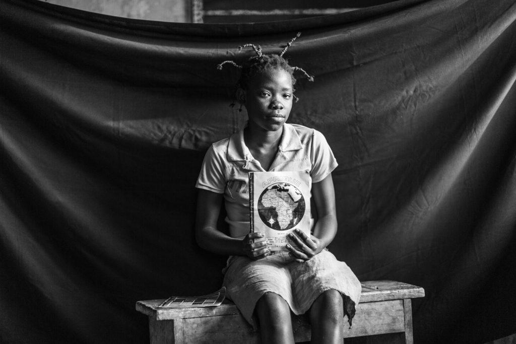 Fideline, 13 años. Ella y su familia huyeron para salvar sus vidas subiendo a un barco en dirección a Batanga, en la República Democrática del Congo. La gota que colmó el vaso fue cuando la adolescente y sus amigos vieron a un hombre de negocios ser ejecutado sumariamente. Fideline recuerda gritar mientras corría hacia su casa. Su padre decidió de inmediato que tenían que irse. «No pude coger ni mi cartera de la escuela, ni mis zapatos, ni las cintas de colores para el pelo, pero sí cogí mis cuadernos y mi bolígrafo», dice la mejor estudiante. «¡Hemos sufrido tanto!», dice. Y añade: «Quiero estudiar para poder convertirme en alguien en la vida».