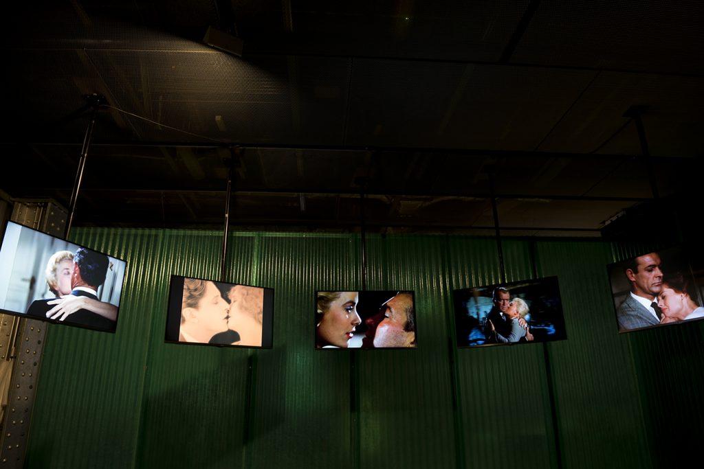 Vista de la exposición con pantallas donde se proyectan escenas de algunas películas del director británico.