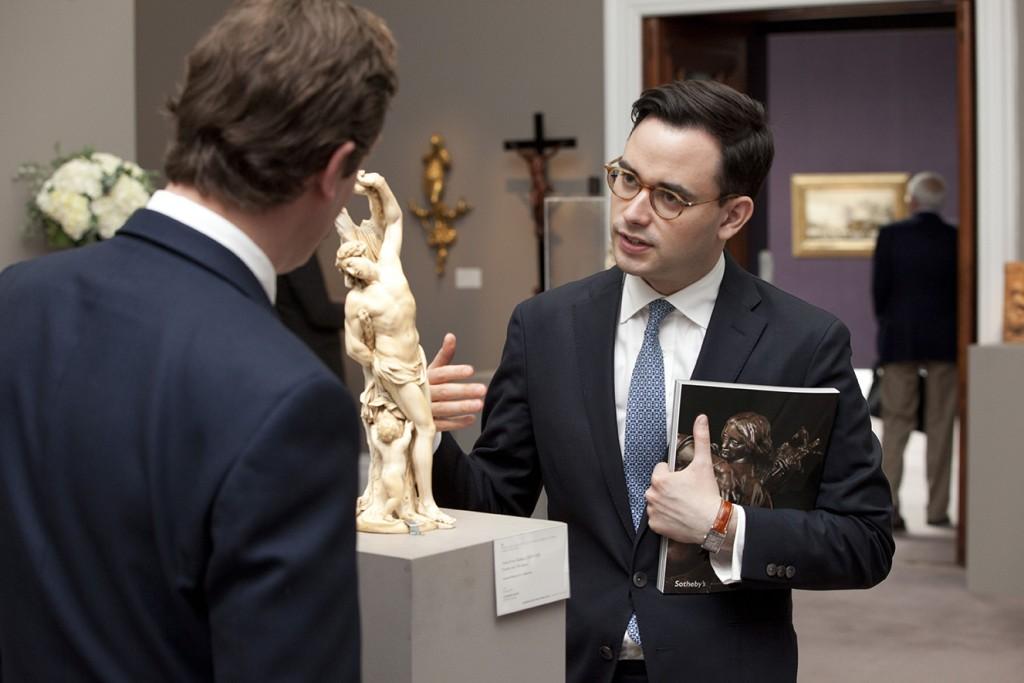 Christopher Mason (de frente) junto a una escultura en Sotheby's.