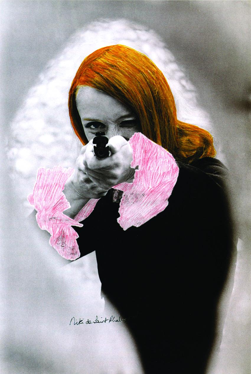 Niki de Saint Phalle apuntando, 1972, fotografía en blanco y negro con retoque de color, extraída de la película Papá. Foto © Peter Whitehead © Niki Charitable Art Foudation, Santee, EE UU.