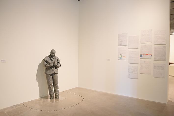 El Chino frotándose las manos de Juan Muñoz expuesto junto al relate que ha inspirado.