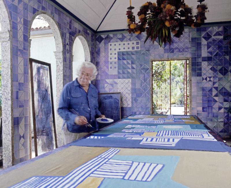 Roberto Burle Marx pintando un mantel en su casa en los años 80. El azulejo de los muros y el candelabro de frutas y flores sobre estructura de y metal son diseños suyos. Fotografía © Tyba