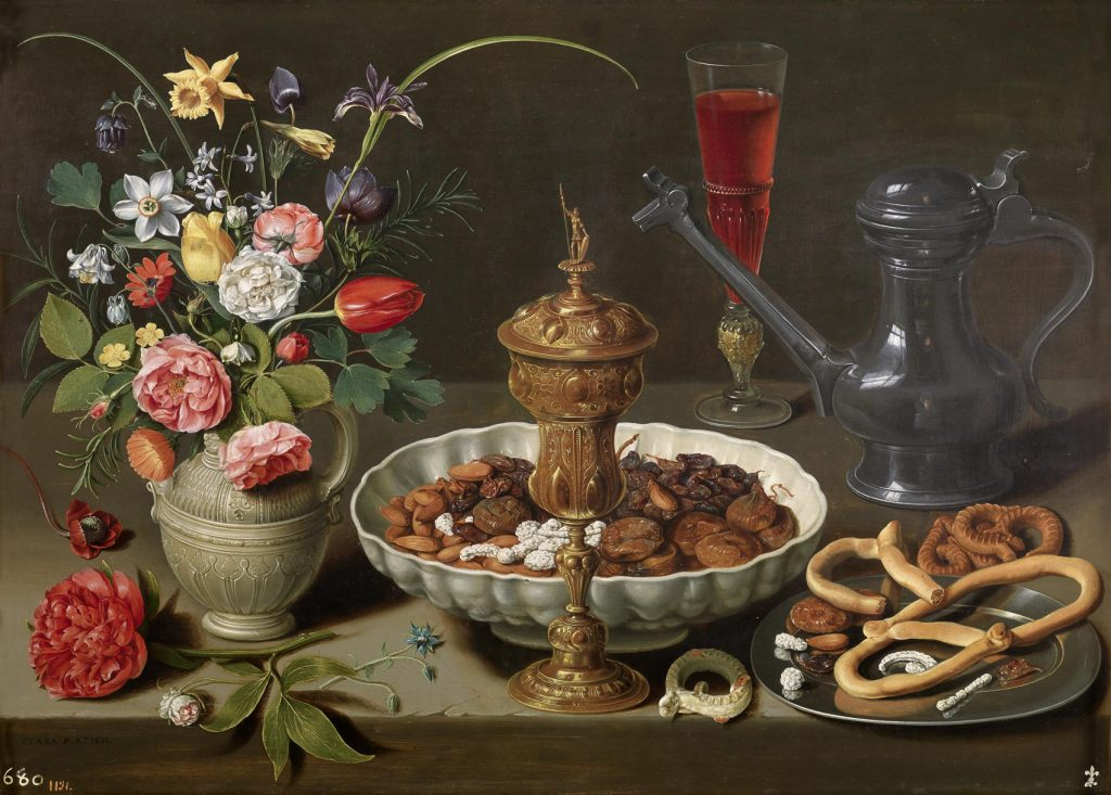 Mesa, hacia 1611, óleo sobre tabla, 52 x 73 cm, Madrid, Museo del Prado. En 1746 la pintura estaba en la colección de pinturas de la reina Isabel Farnesio en el Palacio de La Granja. En la jarra metálica, el reflejo permite ver el exterior del cuadro, donde se autorretrató la artista.
