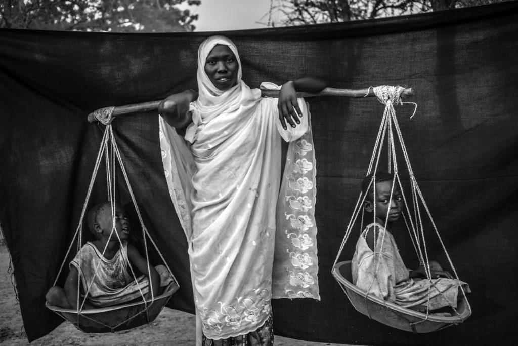 Varios meses antes de que se tomara esta fotografía, los constantes bombardeos obligaron a Dowla, de 22 años, y a sus seis hijos a huir de su pueblo, Gabanit, en el estado de Nilo Azul de Sudán. Lo más importante que pudo llevarse consigo es el palo de madera que balancea por encima de los hombros, con el que transportó a sus seis hijos durante el viaje de diez días que realizaron desde Gabanit hasta Sudán del Sur. En ocasiones, los niños estaban demasiado cansados para andar, lo que la obligaba a cargar a dos de ellos en cada lado. Campamento de refugiados de Doro, en el condado de Maban, Sudán del Sur.