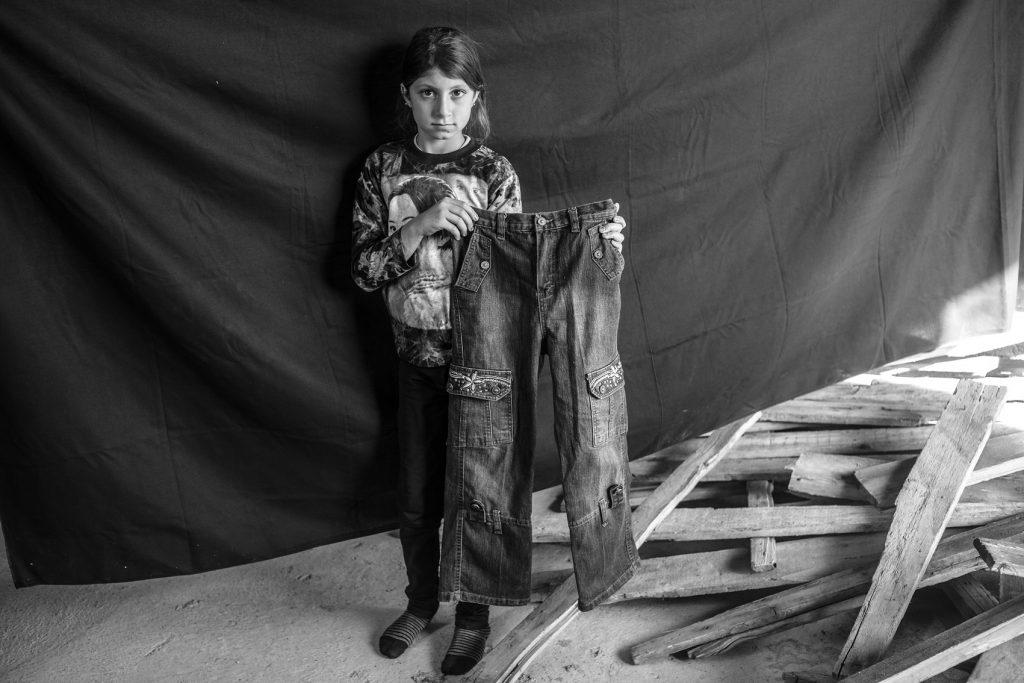 Leila, 9 años, en Erbil, Kurdistán, Iraq (17 de noviembre de 2012). Con sus cuatro hermanas, su madre, su padre y su abuela, llegó a Erbil huyendo de Deir ez-Zor, Siria. Dice, sobre lo más espeluznante antes de su huida: «Era el sonido de los tanques, incluso más aterrador que el de los aviones, porque sentía como que los tanques venían a por mí». Lo más importante que Leila pudo llevarse son los pantalones que sujeta en esta fotografía. «Cuando vi estos pantalones, supe al instante que eran perfectos, porque tienen una flor y me encantan las flores». Solo los ha usado en tres ocasiones, todas ellas en Siria.