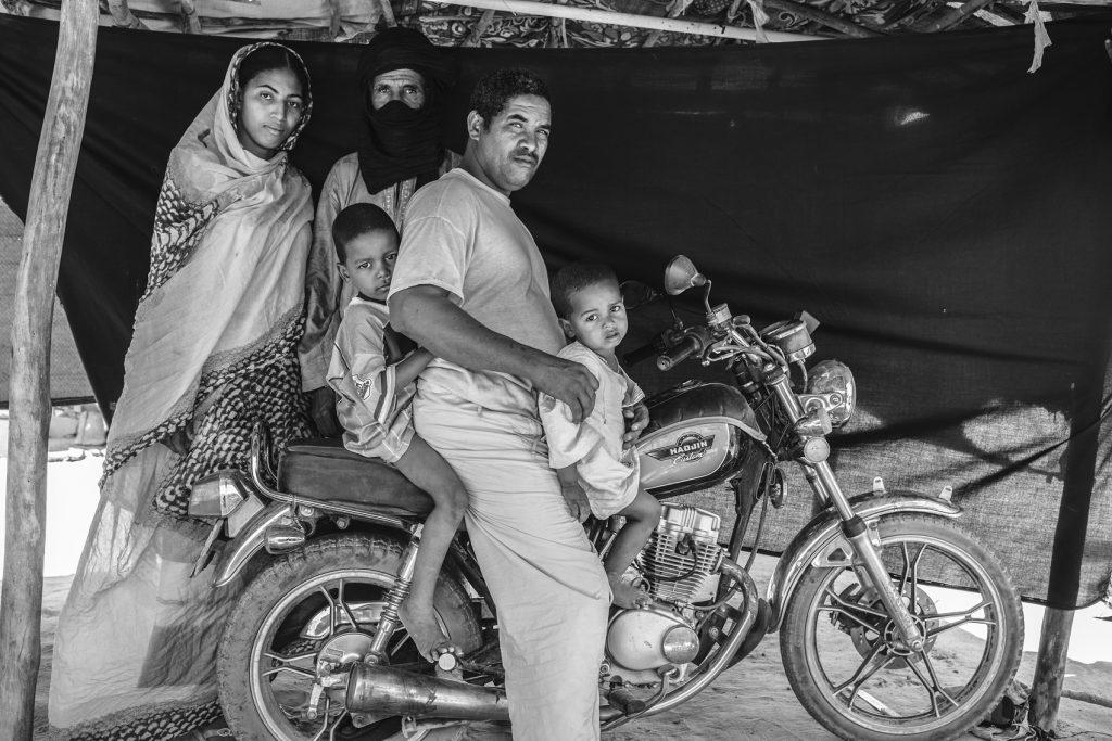 Abdou Ag Moussa, 34 años, en el campo de refugiados de Mentao, Burkina Faso. Abdou está sentado junto a su familia sobre la moto que asegura que le salvó la vida. La familia de Abdou huyó de su casa en Malí después de que su madre y otras cuatro mujeres fueran secuestradas, llevadas al desierto y asesinadas. Cuando Abdou se enteró de lo que había sucedido, esperó a que oscureciera y escapó con su esposa y sus dos hijos al desierto. Volvió a los pocos días para enterrar a su madre, y luego metió a su esposa e hijos en un coche mientras él y su padre les seguían en la moto.