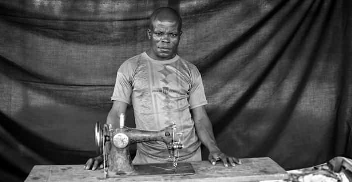 """Benjamin, con su máquina de coser, de la que dice: """"Es mi vida, es mi sangre. La utilizo para poder comprar comida para mi familia"""". En Batanga, gana algún dinero arreglando la ropa de los refugiados y de la población local. Benjamin decidió huir después de ver cómo un combatiente de Seleka mataba de un tiro a un mercader en la zona portuaria de Bangui."""