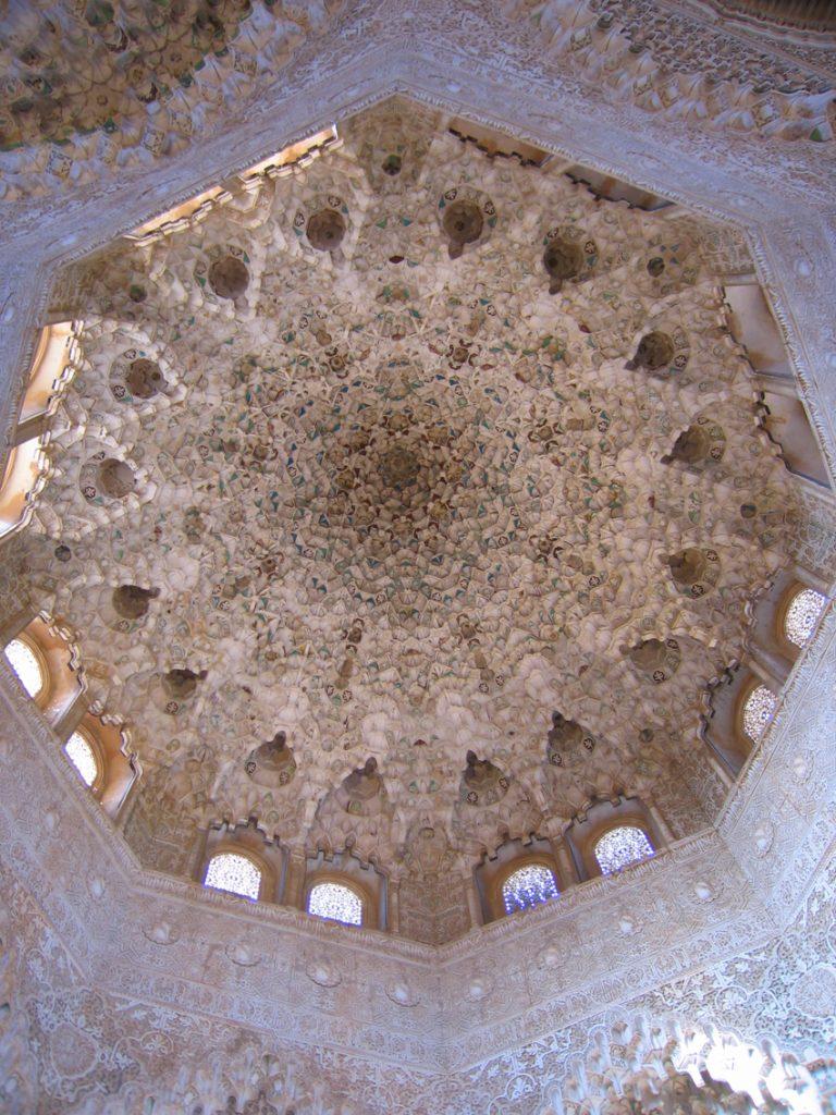 Sobre estas líneas, bóveda de mocárabes de la Sala de las dos Hermanas. Arriba, de izquierda a derecha, vistas de la Alhambra y el Patio de los Leones.